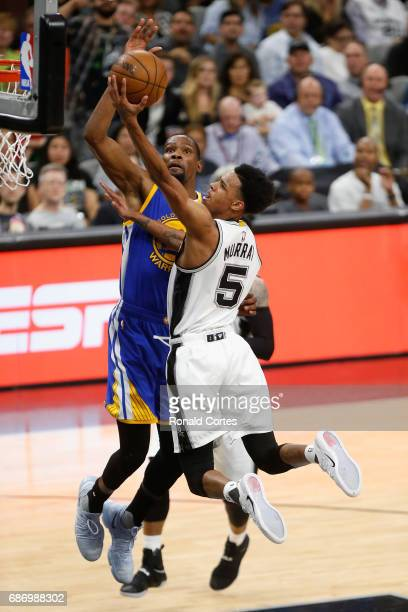 Dejounte Murray of the San Antonio Spurs drives to the basket against Kevin Durant of the Golden State Warriors in the first half during Game Four of...