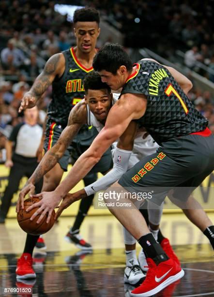 Dejounte Murray of the San Antonio Spurs is tied up by Ersan Ilyasova of the Atlanta Hawks at ATT Center on November 20 2017 in San Antonio Texas...