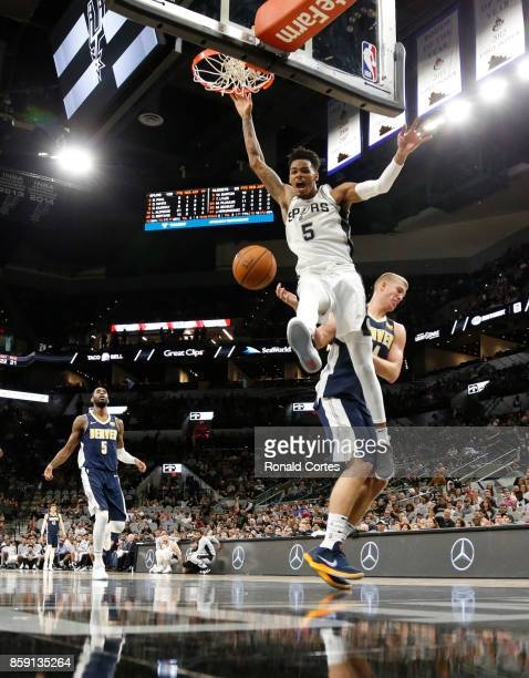 Dejounte Murray of the San Antonio Spurs reacts after dunking over Mason Plumlee of the Denver Nuggets at ATT Center on October 8 2017 in San Antonio...