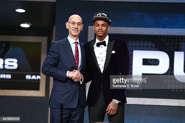 Dejounte Murray shakes hands with NBA Commissioner Adam Silver after being selected number twenty ninth overall by the San Antonio Spurs during the...