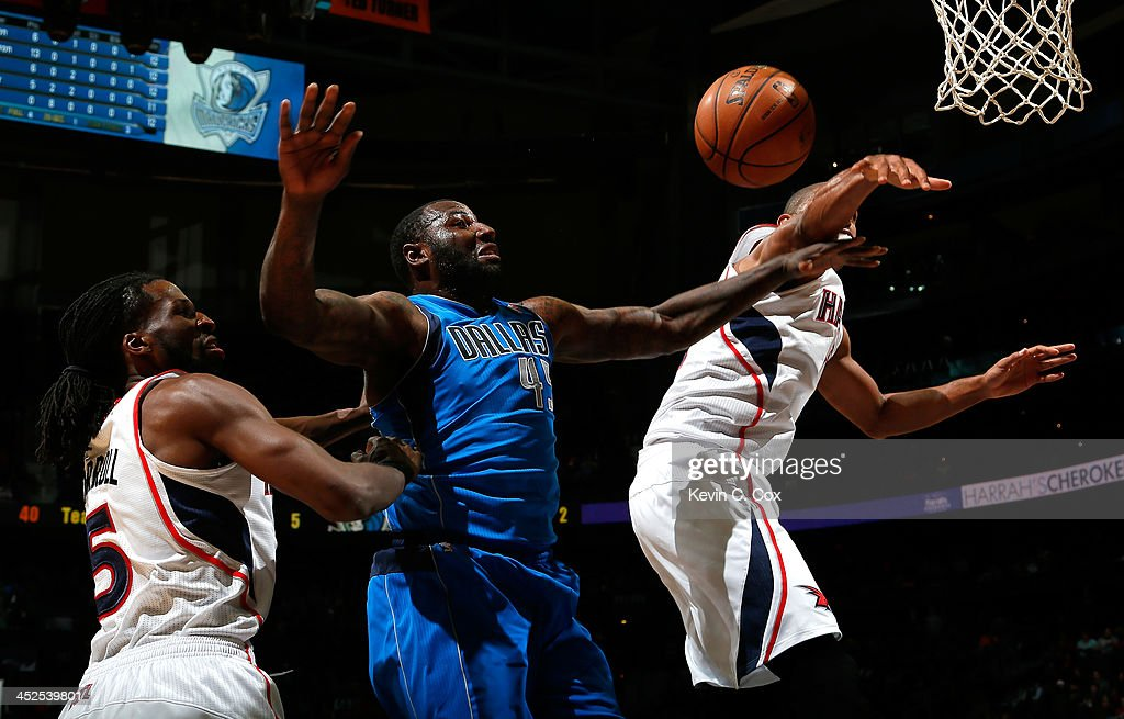 DeJuan Blair #45 of the Dallas Mavericks battles for a rebound against DeMarre Carroll #5 and Al Horford #15 of the Atlanta Hawks at Philips Arena on November 29, 2013 in Atlanta, Georgia.