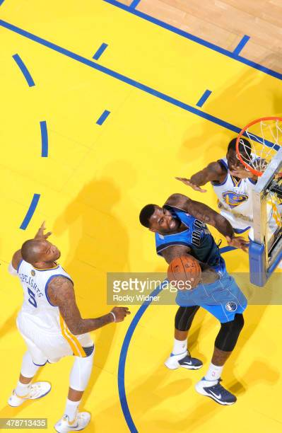 Dejuan Blair of the Dallas Mavericks shoots a layup against Draymond Green of the Golden State Warriors on March 11 2014 at Oracle Arena in Oakland...