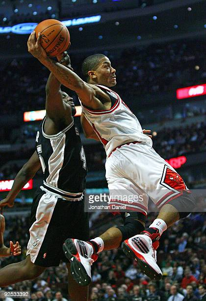 DeJuan Blair of the San Antonio Spurs fouls Derrick Rose of the Chicago Bulls as he goes up for the shot at the United Center on October 29 2009 in...