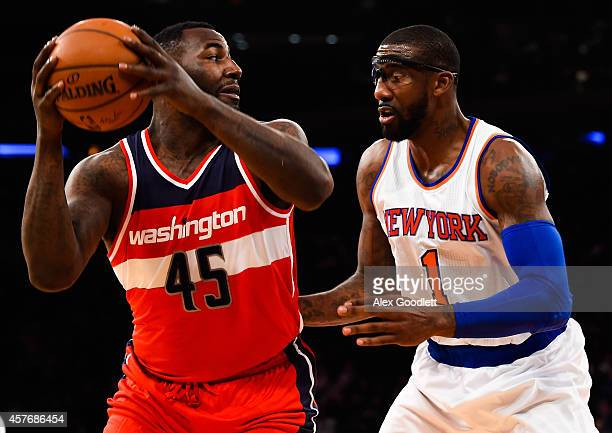DeJuan Blair of the Washington Wizards looks to pass around Amar'e Stoudemire of the New York Knicks in a preseason game at Madison Square Garden on...