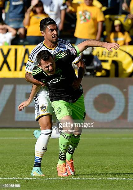 J DeLaGarza of Los Angeles Galaxy holds Marco Pappa of Seattle Sounders FC receiving a yellow card during the Western Conference Final at StubHub...