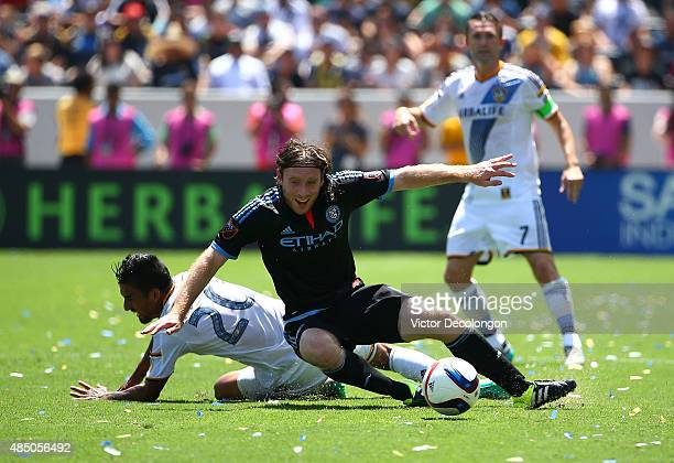 J DeLaGarza of Los Angeles Galaxy tackles Thomas McNamara of New York City FC during the first half of their MLS match at StubHub Center on August 23...