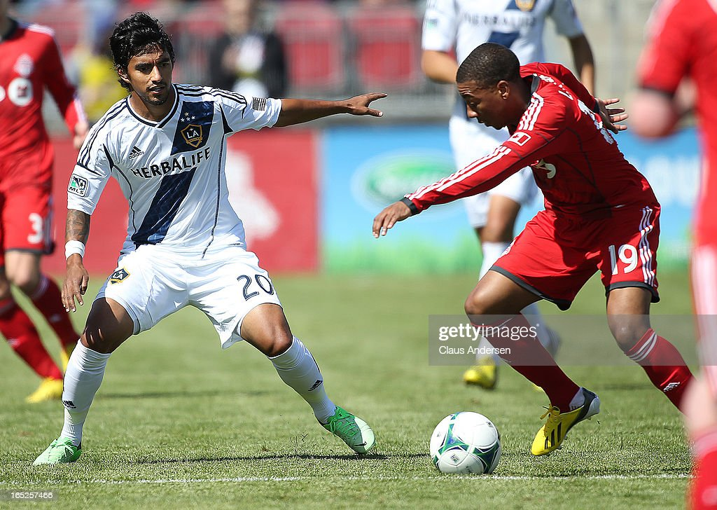 A.J. DeLaGarza #20 of the Los Angeles Galaxy defends against Reggie Lambe #19 of Toronto FC in an MLS game on March 30, 2013 at BMO field in Toronto, Ontario, Canada. The LA Galaxy and the Toronto FC played to a 2-2 tie.