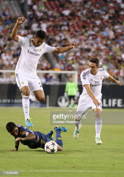 J DeLaGarza of the Los Angeles Galaxy falls to the grass as Carlos Henrique Casimiro of Real Madrid leaps to play the ball during the International...