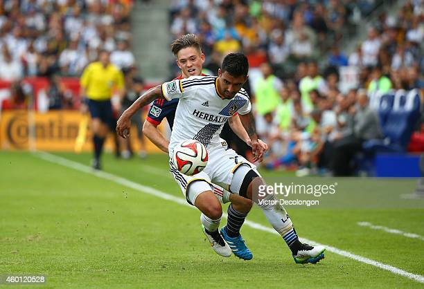 J DeLaGarza of the Los Angeles Galaxy protects the ball from Kelyn Rowe of the New England Revolution in the second half during 2014 MLS Cup at...