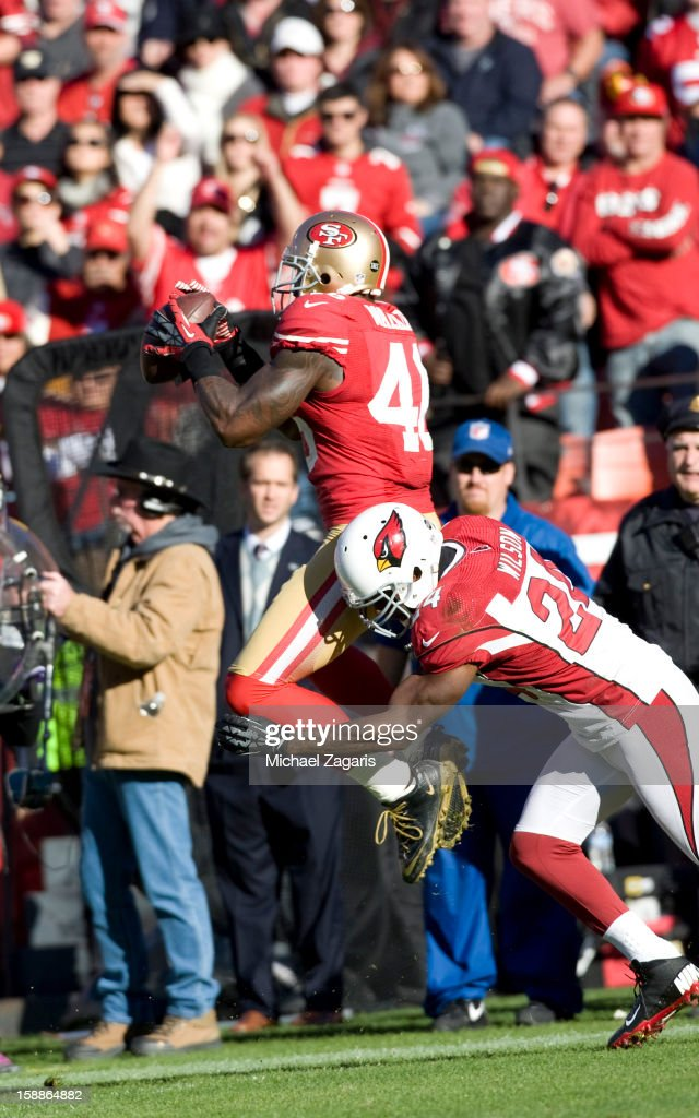 Delanie Walker #46 of the San Francisco 49ers gets hit while making a reception during the game against the Arizona Cardinals at Candlestick Park on December 30, 2012 in San Francisco, California. The 49ers defeated the Cardinals 27-13.