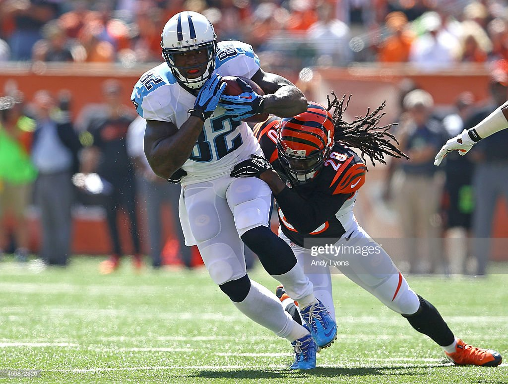 Delanie Walker of the Tennessee Titans is wrapped up by Reggie Nelson of the Cincinnati Bengals during the first quarter at Paul Brown Stadium on...
