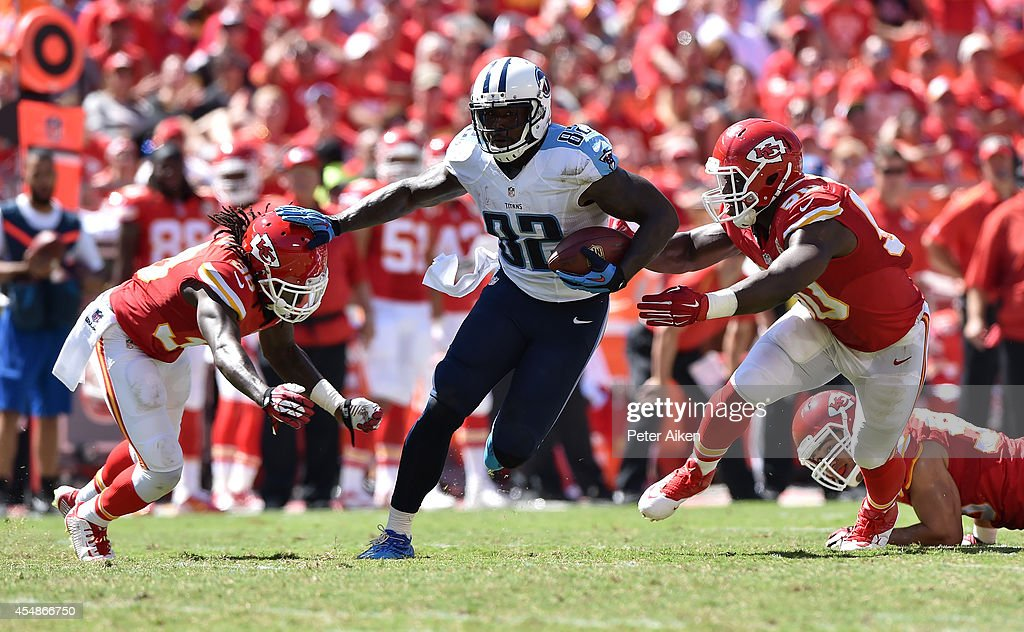 Delanie Walker of the Tennessee Titans runs the ball against Ron Parker and Justin Houston of the Kansas City Chiefs during the second half at...