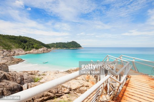 Delapidated pier leading to beach : Stock Photo
