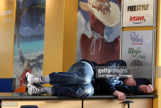 A delayed passenger sleeps on a customer services counter at Stansted Airport Essex following a protest by direct action group Plane Stupid
