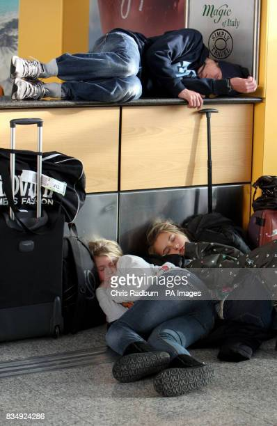Delayed passengers sleeps on a customer services counter at Stansted Airport Essex following a protest by direct action group Plane Stupid
