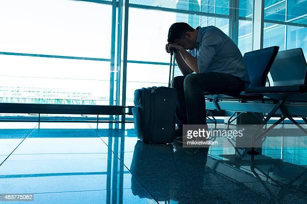 Verspätet Flugzeug macht müde Mann warten in Flughafen mit Koffer