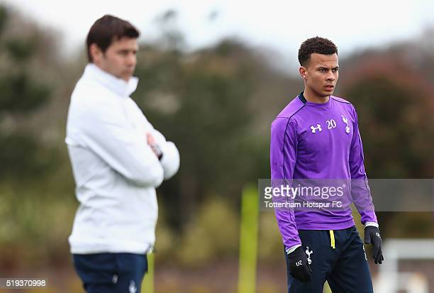Dele Alli looks on next to Mauricio Pochettino during Tottenham Hotspur training session at Hotspur Way on April 6 2016 in Enfield England