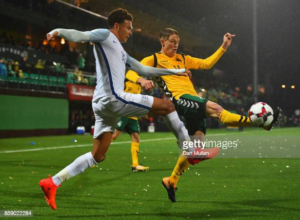 Dele Alli of England and Vykintas Slivka of Lithuania stretch for the ball during the FIFA 2018 World Cup Group F Qualifier between Lithuania and...