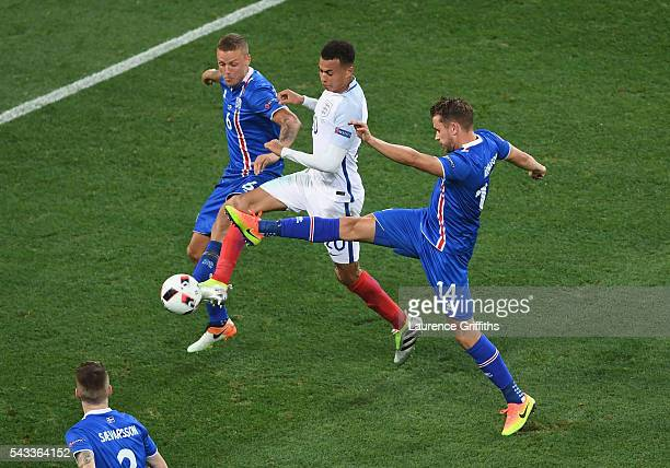 Dele Alli of England competes for the ball against Ragnar Sigurdsson and Kari Arnason of Iceland during the UEFA EURO 2016 round of 16 match between...