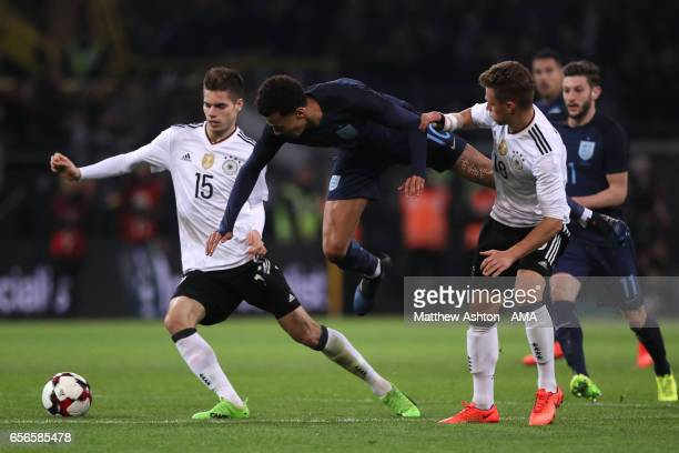 Dele Alli of England competes with Julian Weigl and Joshua Kimmich of Germany during the international friendly match between Germany and England at...