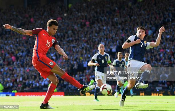 Dele Alli of England shoots as Kieran Tierney of Scotland attempts to block during the FIFA 2018 World Cup Qualifier between Scotland and England at...