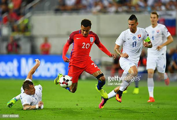 Dele Alli of England takes on Jan Durica and Marek Hamsik of Slovakia during the 2018 FIFA World Cup Group F qualifying match between Slovakia and...