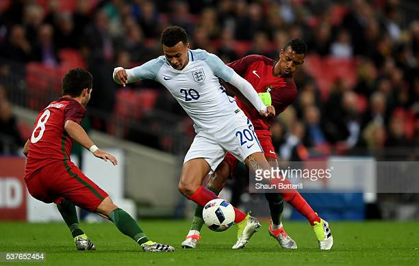 Dele Alli of England takes on Joao Moutinho and Nani of Portugal during the international friendly match between England and Portugal at Wembley...