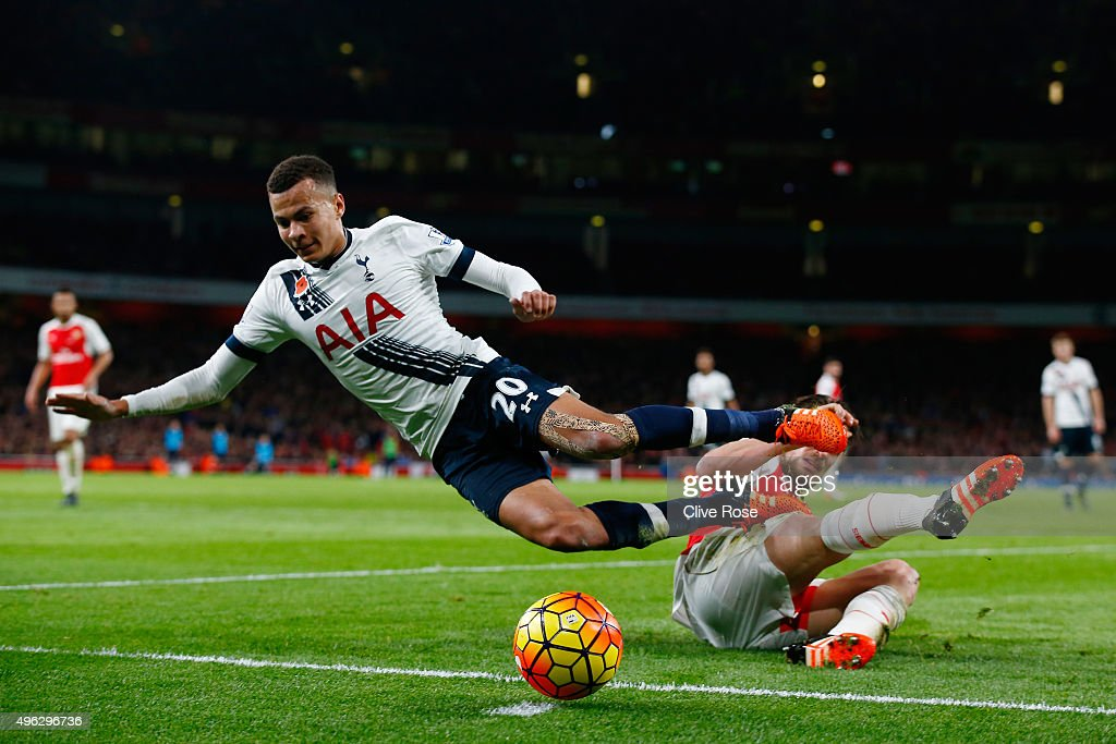 Dele Alli of Spurs is tackled by Mathieu Debuchy of Arsenal during the Barclays Premier League match between Arsenal and Tottenham Hotspur at the Emirates Stadium on November 8, 2015 in London, England.