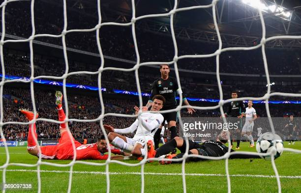 Dele Alli of Tottenham Hotspur beats Francisco Casilla of Real Madrid as he scores their first goal during the UEFA Champions League group H match...