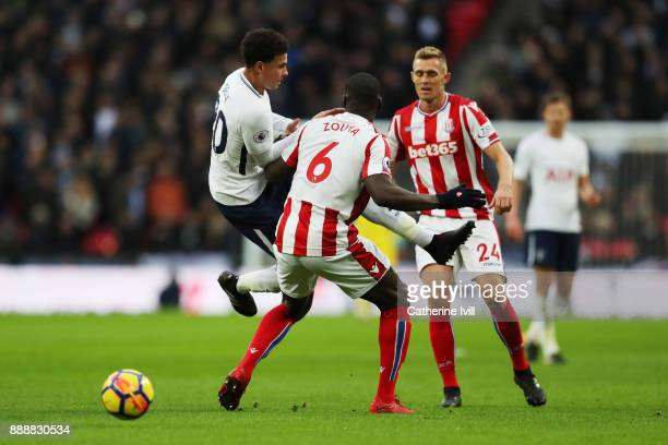 Dele Alli of Tottenham Hotspur is challenged by Darren Fletcher of Stoke City and Kurt Zouma of Stoke City during the Premier League match between...