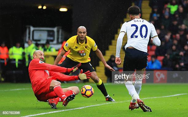 Dele Alli of Tottenham Hotspur shoots past Heurelho Gomes of Watford as he scores their third goal during the Premier League match between Watford...
