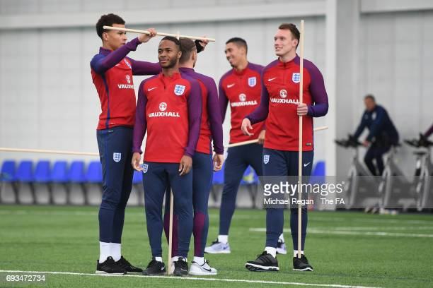Dele Alli uses a stick to compare the height of Raheem Sterling and Kieran Trippier during the England training session at St Georges Park on June 7...