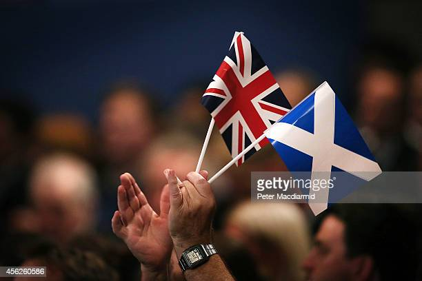 A delegate applauds speeches at the Conservative party conference holding both a Union and Scottish Saltire flag on September 28 2014 in Birmingham...
