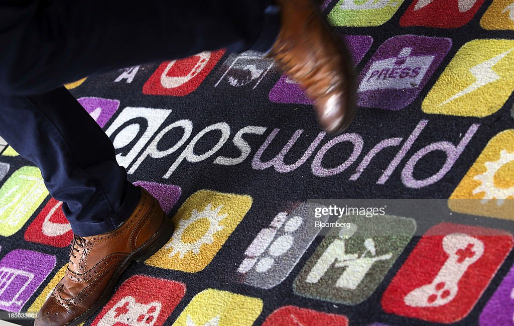 A delegate crosses an appsworld logo on a carpet during the Apps World Multi-Platform Developer Show in London, U.K., on Wednesday, Oct. 23, 2013. Retail sales of Internet-connected wearable devices, including watches and eyeglasses, will reach $19 billion by 2018, compared with $1.4 billion this year, Juniper Research said in an Oct. 15 report. Photographer: Chris Ratcliffe/Bloomberg via Getty Images