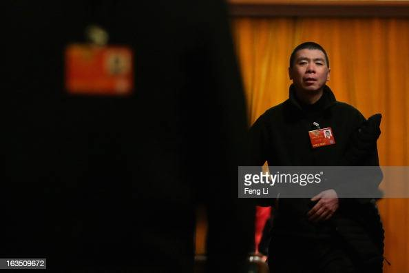 Delegate Feng Xiaogang Chinese famous director leaves the meeting room during the plenary session of the Chinese People's Political Consultative...