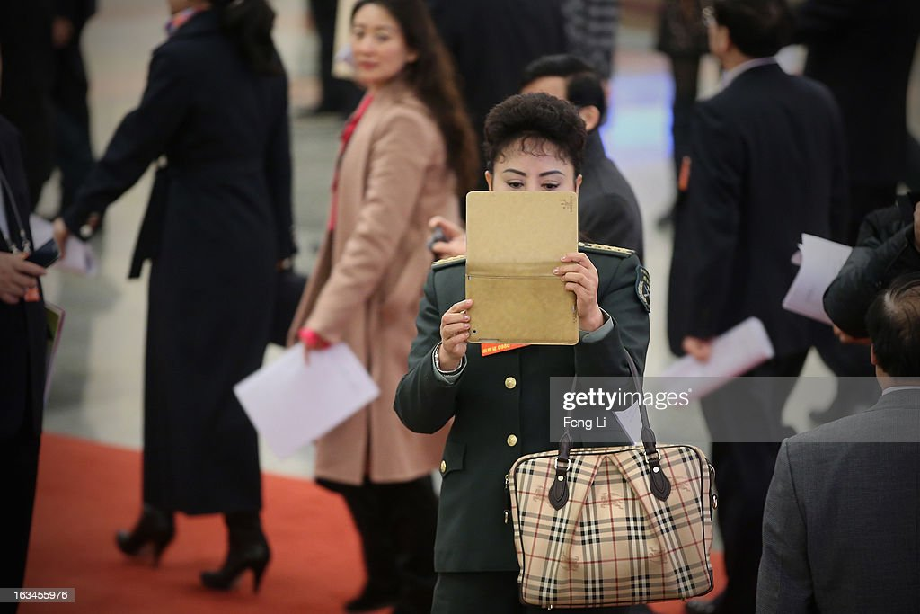 A delegate from Chinese People's Liberation Army carrying a Burberry bag takes pictures with her iPad as she arriving at the Great Hall of the People to attend a plenary session of the National People's Congress on March 10, 2013 in Beijing, China. The State Council, China's cabinet, will begin its seventh restructuring attempt in the past three decades to roll back red tape and reduce administrative intervention. Several departments under the State Council will be reorganized according to a plan on the institutional restructuring and functional transformation of the State Council, which was submitted to the plenary session of the National People's Congress Sunday.