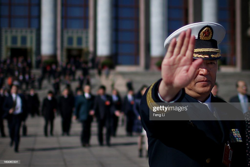 A delegate from Chinese People's Liberation Army raises his hand to stop taking pictures after attending a pre-opening session of the National People's Congress, China's parliament, at the Great Hall of the People on March 4, 2013 in Beijing, China. China's defensive military policies have played a core role in maintaining peace and stability in Asia, a spokesperson for the annual session of China's national legislature said Monday.