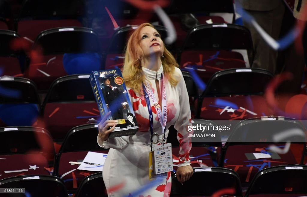 TOPSHOT - A delegate holds a Trump doll as she looks up after the final night of the Republican National Convention at the Quicken Loans Arena in Cleveland, Ohio on July 21, 2016. /