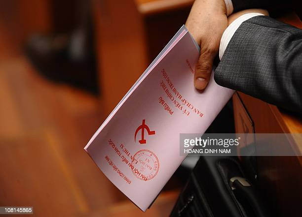 A delegate holds his ballot as he waits to vote the Vietnam Communist Party 's new Central Committee members in during the 11th national congress of...