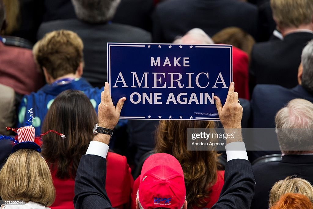 """A Republican Convention delegate holds up a sign saying """"Make America One Again"""""""