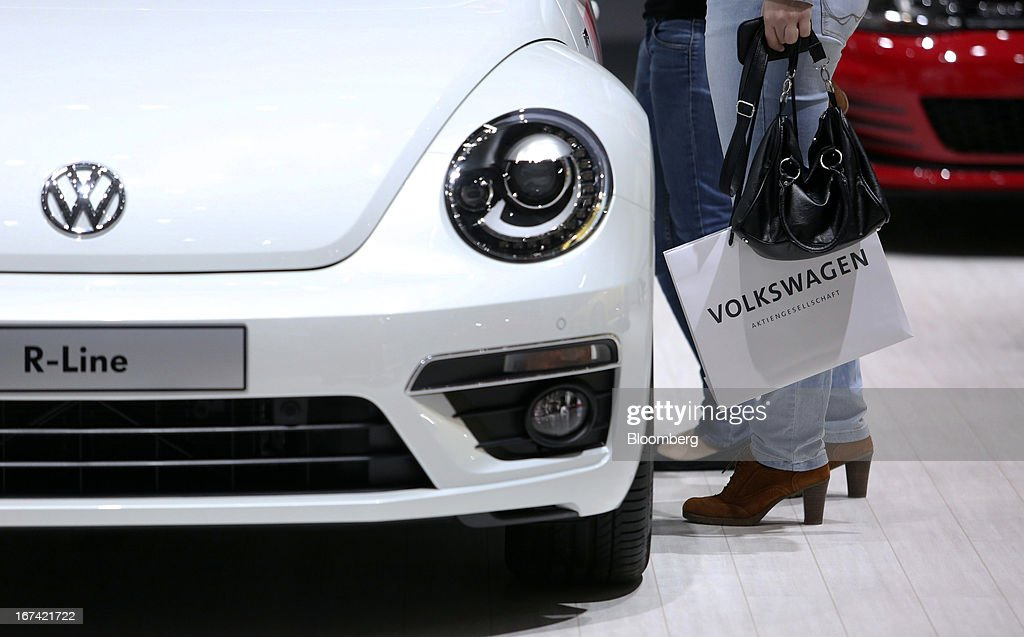 A delegate looks inside a Volkswagen Beetle R-Line automobile at the Volkswagen AG annual general meeting (AGM) in Hanover, Germany, on Thursday, April 25, 2013. Volkswagen AG, Europe's biggest automaker, aims to offset plunging European demand this year by rolling out 60 new and updated models, including luxury cruisers like the Bentley Flying Spur. Photographer: Chris Ratcliffe/Bloomberg via Getty Images