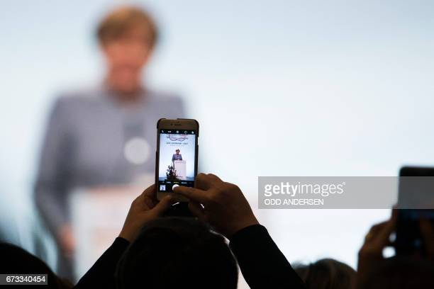 TOPSHOT A delegate makes a picture of German Chancellor Angela Merkel speaking at the Women 20 summit 2017 in Berlin on April 26 2017 / AFP PHOTO /...
