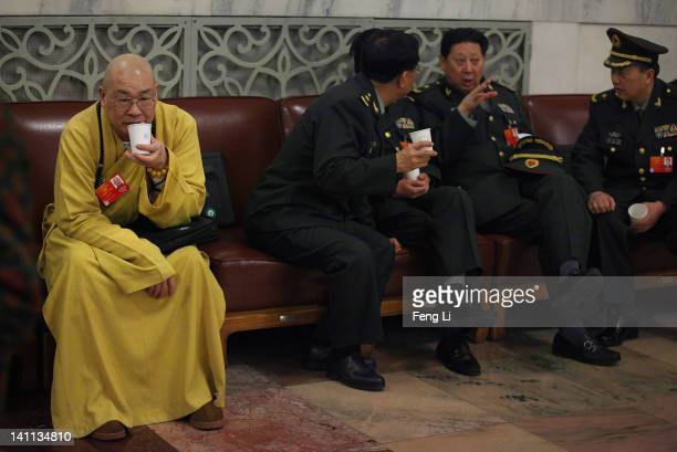 A delegate of Buddhist monk and Chinese military delegates arrive at The Great Hall Of The People before the fourth plenary meeting of the National...