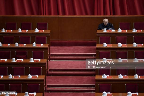 A delegate reads a document before the opening session of the Chinese Communist Party's fiveyearly Congress at the Great Hall of the People in...