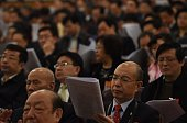 A delegate reads through Chinese Premier Li Keqiang's work report during the opening session of the National People's Congress in the Great Hall of...