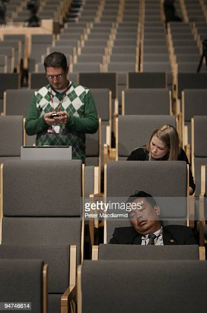 A delegate sleeps in the main press conference room as journalists wait for news on the final day of the UN Climate Change Conference on December 18...