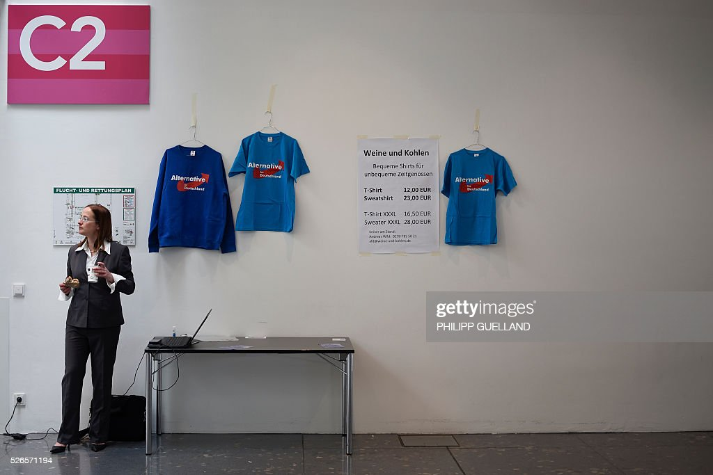 A delegate stands next to merchandise shirts on display at the venue of the german right wing party Alternative for Germany (AfD) at the the Stuttgart Congress Centre ICS on April 30, 2016. The Alternative for Germany (AfD) party is meeting in the western city of Stuttgart, where it is expected to adopt an anti-Islamic manifesto, emboldened by the rise of European anti-migrant groups like Austria's Freedom Party. / AFP / Philipp GUELLAND