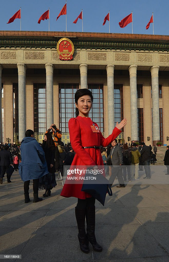 Delegate Sun Wei from Shaanxi Province poses for photos before the opening session of the National People's Congress (NPC) at the Great Hall of the People in Beijing on March 5, 2013. Chinese Premier Wen Jiabao on March 5 targeted 2013 growth of 7.5 percent and vowed an unwavering fight against corruption as the world's second-largest economy opened its annual parliamentary session. AFP PHOTO/Mark RALSTON