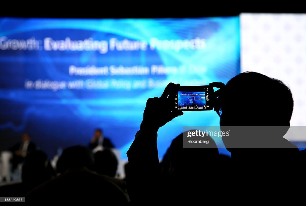 A delegate takes a photograph using his mobile device at the Asia-Pacific Economic Cooperation (APEC) CEO Summit in Nusa Dua, Bali, Indonesia, on Sunday, Oct. 6, 2013. Global growth will probably be slower and less balanced than desired, ministers from the APEC member economies said as they agreed to refrain from raising new barriers to trade and investment. Photographer: SeongJoon Cho/Bloomberg via Getty Images