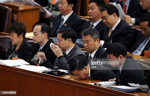 A delegate takes a rest while listening to a speech during the National People's Congress at the Great Hall of the People in Beijing on March 10 2013...